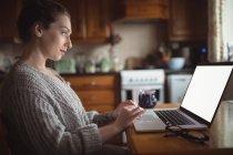 Hermosa mujer usando el ordenador portátil en la mesa en la cocina en casa - foto de stock