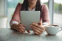 Seção média da mulher usando tablet digital enquanto toma xícara de café — Fotografia de Stock