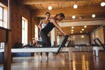 Entrenador ayudando a una mujer mientras practica pilates en un gimnasio - foto de stock