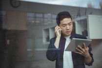 Business executive talking on mobile phone while using digital tablet in office — Stock Photo