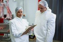 Metzger interagieren in Fleischfabrik miteinander — Stockfoto