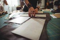 Meados de seção de artesão organizando peça de couro na mesa de trabalho na oficina — Fotografia de Stock