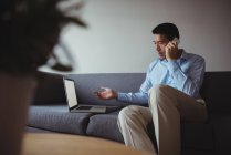 Man talking on mobile phone while using laptop in living room at home — Stock Photo