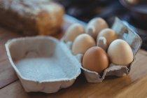 Close-up de ovos em caixa de ovo em mesa de madeira — Fotografia de Stock