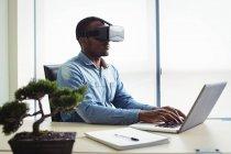 Business Executive utilisant un casque de réalité virtuelle et travaillant sur un ordinateur portable au bureau — Photo de stock