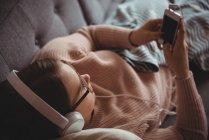 Femme allongée sur un canapé écoutant de la musique sur un téléphone portable dans le salon à la maison — Photo de stock
