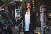 Фронтальний вид красива жінка, стоячи біля автомобіля в електричного автомобіля зарядний — стокове фото