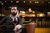 Uomo guardando un bicchiere di vino rosso nel bar — Foto stock