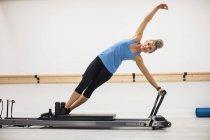 Mujer adulta haciendo ejercicio sobre reformador en el gimnasio - foto de stock