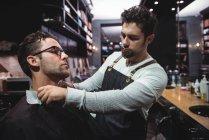 Парикмахер ставит плащ над клиентом в парикмахерской — стоковое фото