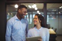 Empresario y un colega discutiendo sobre tableta digital en la oficina - foto de stock