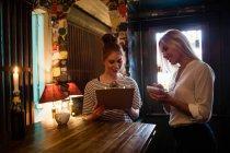Офіціантка обговорювати меню з клієнтом в рядку — стокове фото