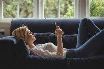Женщина лежит на диване и пользуется мобильным телефоном в гостиной дома — стоковое фото