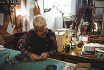 Внимательная ремесленница режет кусок кожи в мастерской — стоковое фото