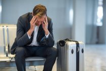 Tense businessman sitting in waiting area with luggage at airport terminal — Stock Photo