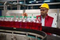 Впевнено чоловік співробітника огляду пляшок сік заводі — стокове фото