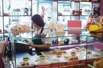 Female shopkeeper using cash register in shop — Stock Photo