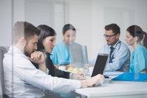 Ärzte diskutieren bei Besprechung im Konferenzraum über Laptop — Stockfoto