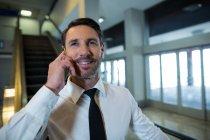 Empresario en escalera mecánica hablando por teléfono móvil en el aeropuerto - foto de stock
