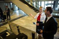 Жіночий персонал, показуючи напрям бізнесмен в аеропорту терміналу — стокове фото