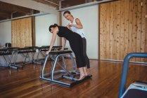 Allenatrice donna che assiste la donna mentre pratica pilates in palestra — Foto stock
