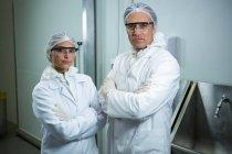 Técnicos de pie con los brazos cruzados en fábrica de carne - foto de stock