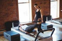 Инструктор, помогающий женщине во время занятий пилатесом в фитнес-студии — стоковое фото