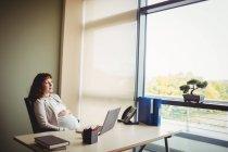 Femme d'affaires enceinte touchant le ventre au bureau — Photo de stock