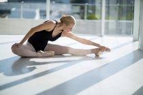 Балерина, виконуючи розкол у світлі студії — стокове фото