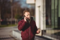Esecutivo maschile che parla al cellulare sulla strada di fronte all'edificio degli uffici — Foto stock