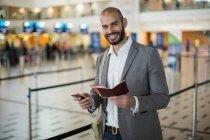 Uomo d'affari sorridente in possesso di una carta d'imbarco e controllare il suo telefono cellulare al terminal dell'aeroporto — Foto stock