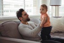 Padre jugando con su bebé en el sofá en la sala de estar en casa — Stock Photo