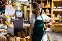 Female staff standing at bread counter in supermarket — Stock Photo