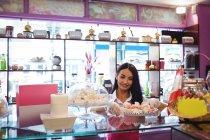 Владелица магазина держит в магазине поднос с турецкими сладостями — стоковое фото