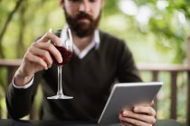 Man using digital tablet while having glass of wine in bar — Stock Photo