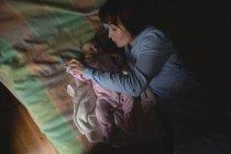 Madre che gioca con il bambino sul lenzuolo in camera da letto a casa — Foto stock