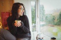 Улыбающаяся женщина держит чашку кофе на кухне дома — стоковое фото