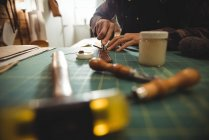 Mid-section of craftswoman cutting leather in workshop — Stock Photo