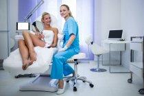 Femme dermatologue et patiente souriant à la caméra à la clinique — Photo de stock