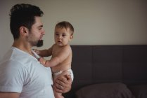 Man holding his baby while standing in living room at home — Stock Photo