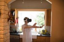 Женщина жестикулирует, используя гарнитуру виртуальной реальности дома — стоковое фото