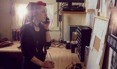 Female hairdresser talking on mobile phone in dreadlocks shop — Stock Photo