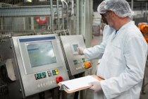 Männliche Arbeiter inspizieren Produkte in Kaltgetränkfabrik — Stockfoto