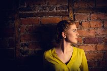Mulher bonita de pé contra a parede de tijolo — Fotografia de Stock