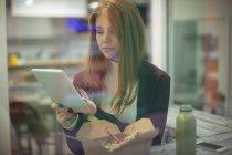 Donna che usa tablet digitale mentre mangia insalata nel ristorante — Foto stock