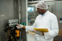 Male worker holding clipboard while operating machine in juice factory — Stock Photo