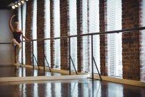 Ballerina practicing ballet dance at barre in ballet studio — Stock Photo