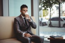 Businessman having coffee while sitting on sofa in the office — Stock Photo