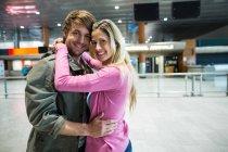 Retrato de pareja sonriente abrazándose en la sala de espera en la terminal del aeropuerto - foto de stock
