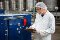 Ernsthafter männlicher Arbeiter inspiziert Maschinen in Kaltgetränkfabrik — Stockfoto